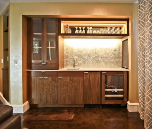 Walnut wet bar with sink, wine cooler, frig, special lighting, metal back glass back