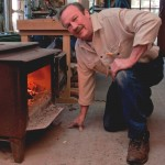 Don bent down at  wood stove